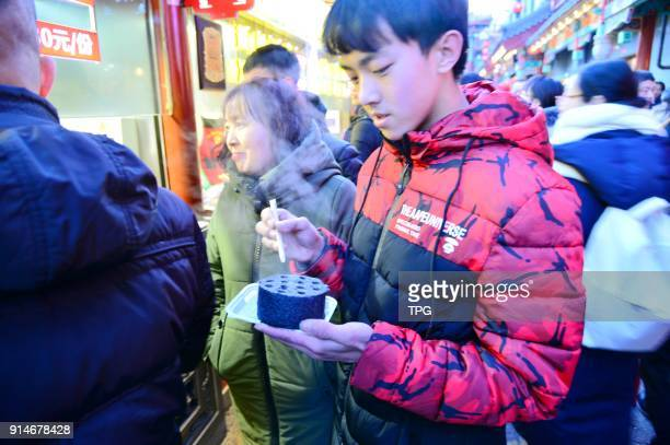The unique honeycomb briquette cake attracts many people to eat on 05th February 2018 in Beijing China