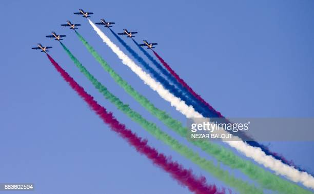 The United Arab Emirates' AlFursan National Aerobatic Team performs with smoke along the corniche of the capital Abu Dhabi on December 1 during...