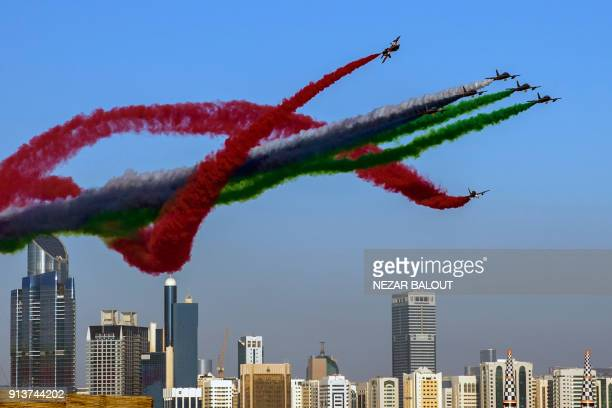TOPSHOT The United Arab Emirates' AlFursan National Aerobatic Team performs with smoke with the colours of the UAE flag during the 2018 Red Bull Air...