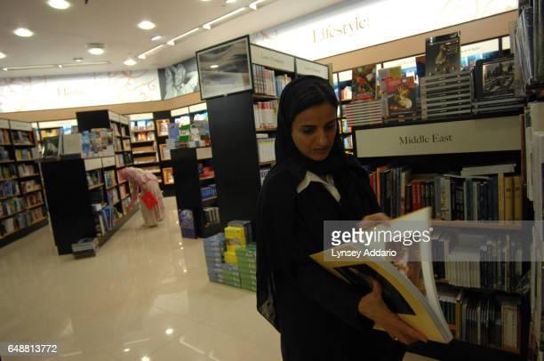 The United Arab Emirates' Minister of Economics Sheikha Lubna Khalid Al Qasimi browses through books inside her office building in Abu Dhabi United...