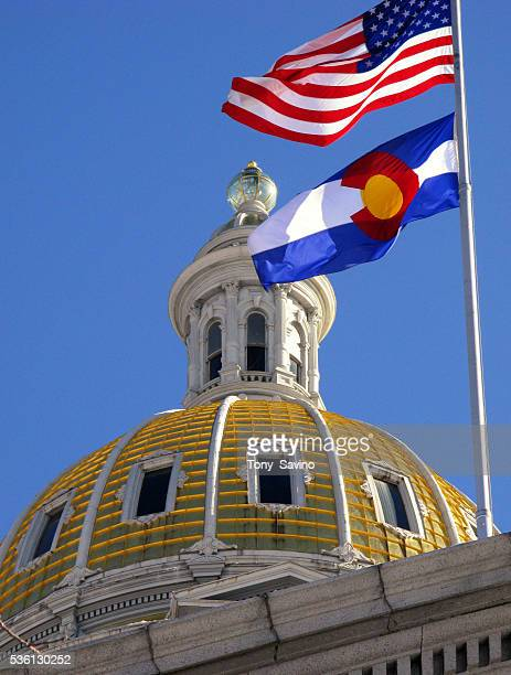 The United States and Colorado state flags fly near the gold dome of the State Capitol building