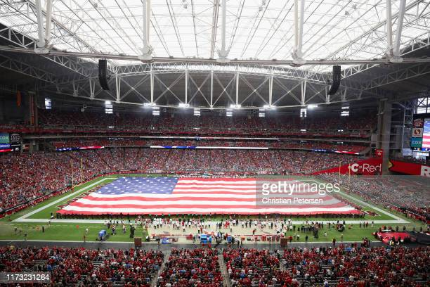 The United States flag is held on the field for the national anthem before the NFL game between the Arizona Cardinals and the Detroit Lions at State...