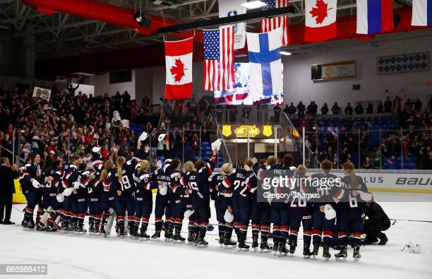 The United States watches their flag rise after a 3-2 overtime win over Canada in the gold medal game at the 2017 IIHF Woman's World Championships at...