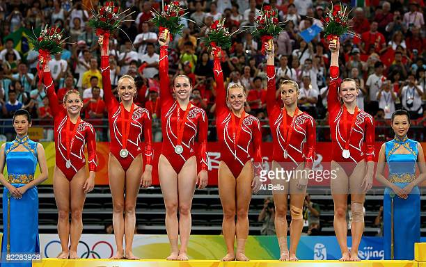 The United States women's gymnastics team wave to the crowd after receiving the silver medal in the artistic gymnastics team event at the National...