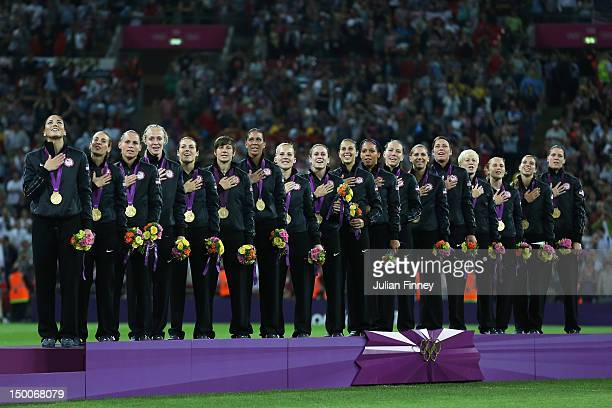 The United States women's soccer team listens to the national anthem with the the gold medal after defeating Japan by a score of 21 to win the...