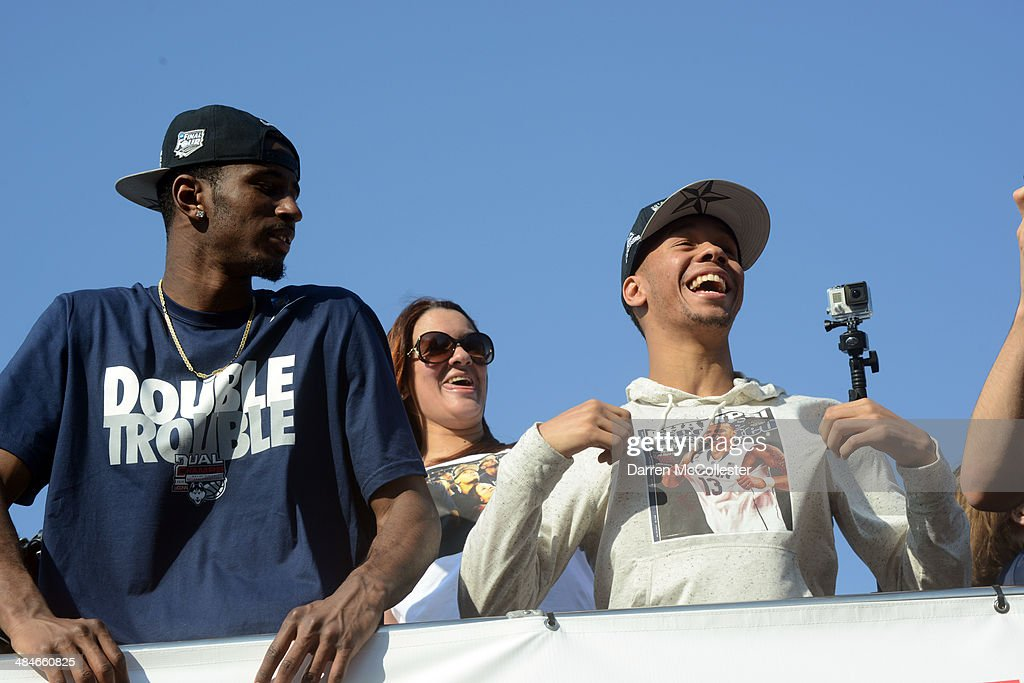 The University of Connecticut's Shabbaz Napier (R) and DeAndre Daniels ride in a victory parade to celebrate their team's national championship April 13, 2014 in Hartford, Connecticut. This year was the second time both the men's and women's Uconn basketball teams have won national championships in the same year.