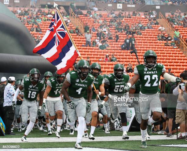 The University of Hawaii Rainbow Warriors run on the the field before their first home game of the season against the Western Carolina Catamounts at...