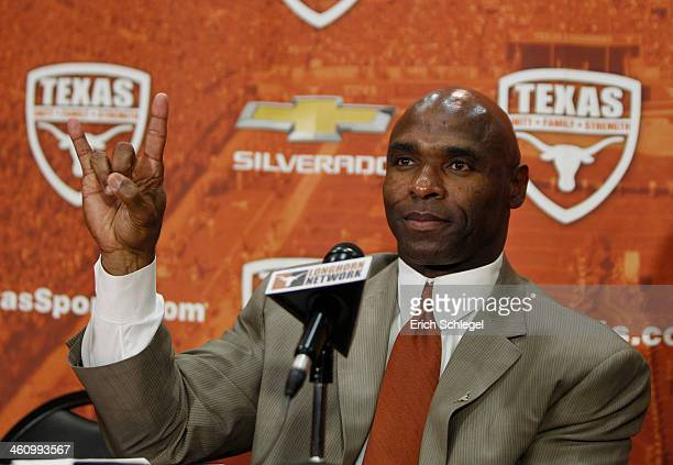 The University of Texas Longhorns new head football coach Charlie Strong from Louisville flashes the Hook 'Em Horns sign after being introduced...