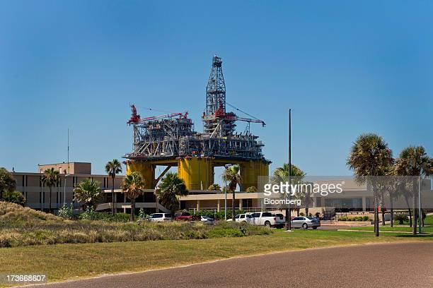 The University of Texas Marine Science Institute stands as the Royal Dutch Shell Plc Olympus tension leg platform sails through Port Aransas Texas US...