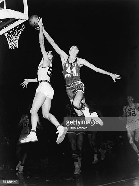 The University of West Virginia's Jerry West soaring through the air to prevent the University of Kentucky's Adrian Smith from making a layup during...