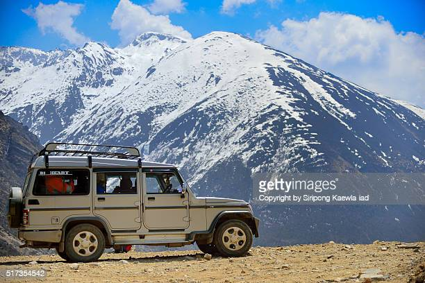 The unknown tourist jeep parking with snowcapped mountain in background