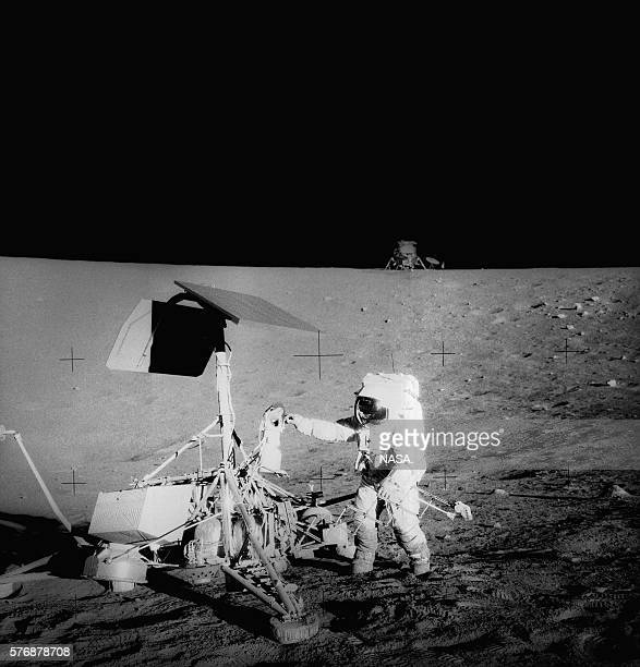 The unmanned Surveyor III lunar lander photographed by the astronauts of Apollo 12 Their landing craft the Intrepid sits on the horizon | Location...