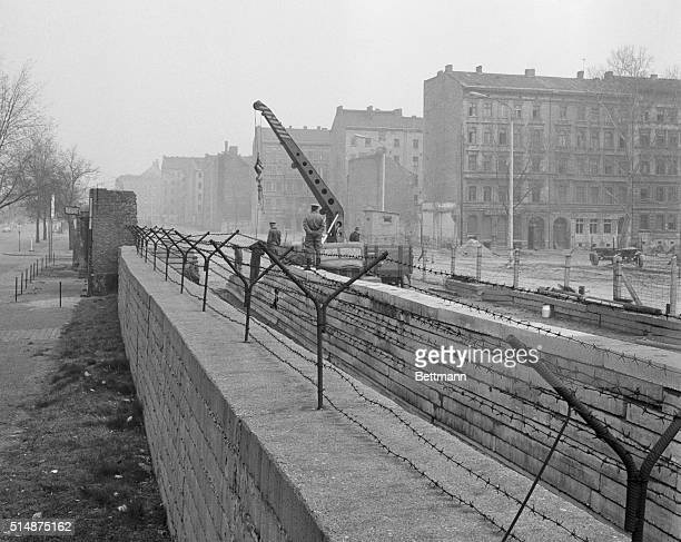 The unrelenting East Berlin barrier is still being reinforced as workers erect a second wall of concrete The new building site is behind the old wall...