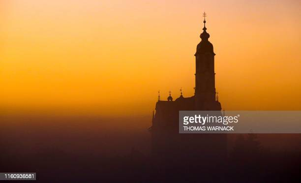TOPSHOT The Unserer Lieben Frau pilgrimage church silhouettes against the sky painted in golden light as sun rises over Steinhausen southern Germany...