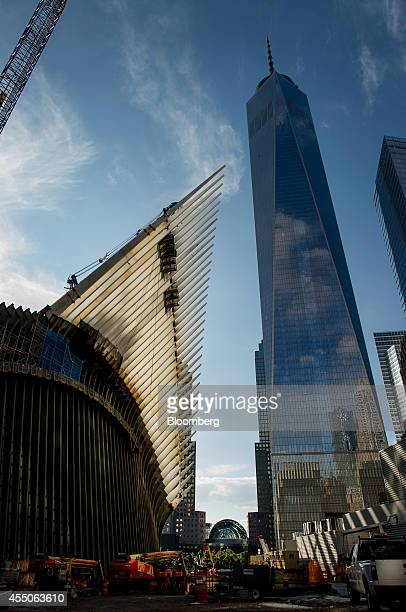The upper portion of the World Trade Center Transportation Hub under construction left and One World Trade Center stand in New York US on Sunday Sept...
