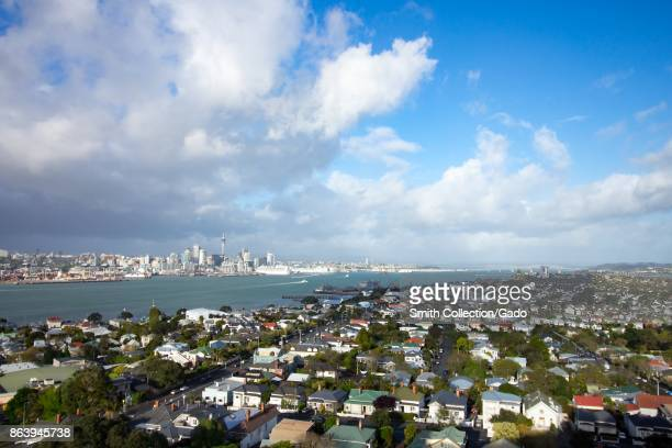 The urban skyline and surrounding neighborhoods of Auckland New Zealand as well as Auckland Harbor are visible from Mount Victoria under a dramatic...