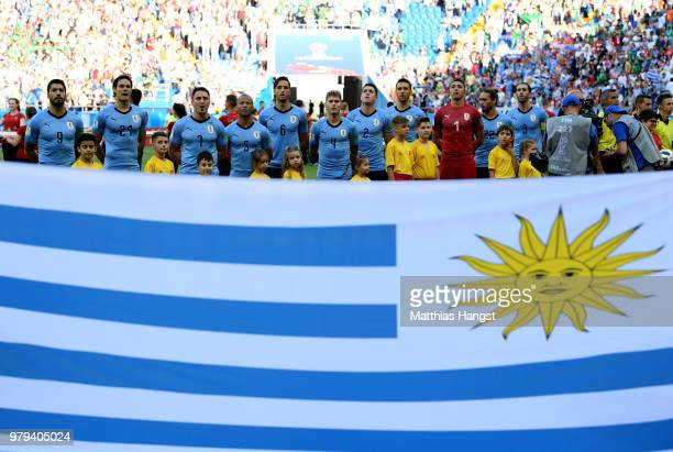 The Uruguay team are seen from behind a Uruguay flag during the national anthems prior to the 2018 FIFA World Cup Russia group A match between...
