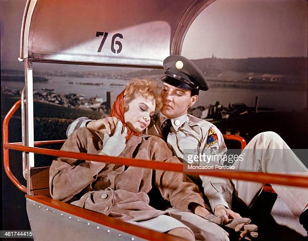 The US actor and singer Elvis Presley is lovingly embracing the actress Juliet Prowse while he is seated next to her on a boat in a scene of the film...