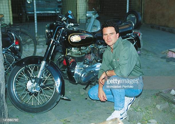 The US actor Ethan Wayne squatting next to a motorbike in a garage 1992