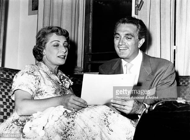 The US actor Robert Alda and the Italian actress Andreina Pagnani are seated next to the other and are reading a page of a script Italy