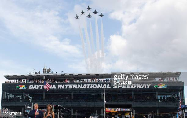 The US Air Force Thunderbirds perform a flyover as US President Donald Trump and First Lady Melania Trump stand for the National Anthem as they...