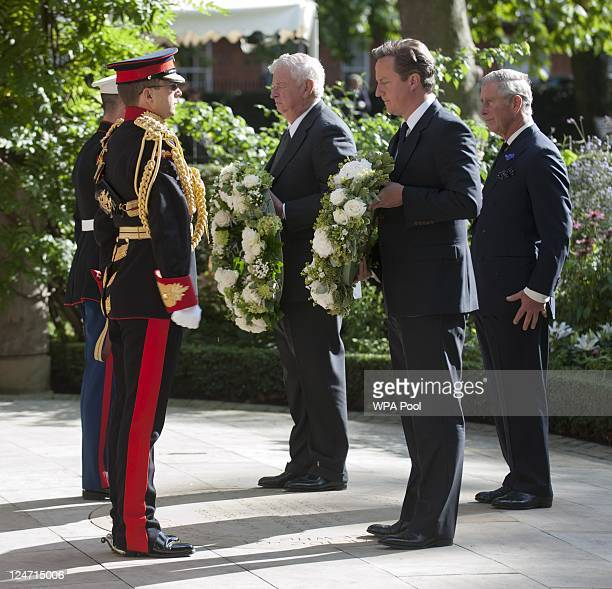 The US Ambassador Louis Susman Prime Minister David Cameron and Prince Charles Prince of Wales lay wreaths at a memorial ceremony at the September 11...