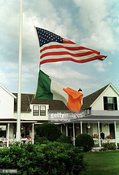 The US and an Irish tricolor fly at half staff in front of a house in the neighborhood near the Kennedy family compound 22 July 1999 in Hyannis Port...