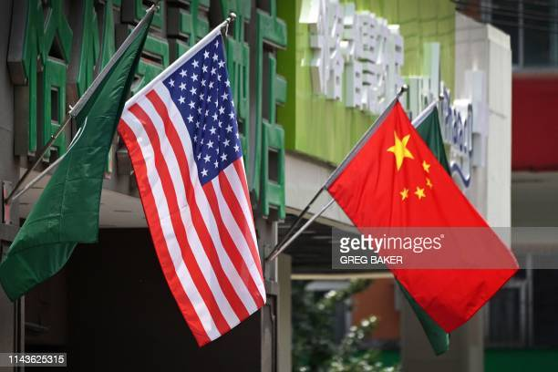 The US and Chinese flags are displayed outside a hotel in Beijing on May 14 2019 Beijing's latest retaliation against US tariff hikes an increase on...