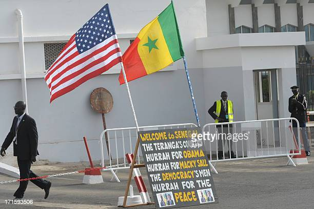 The US and Senegalese flags are flown above a sign welcoming US President Barack Obama and US First Lady Michelle Obama on June 26 2013 in Dakar US...
