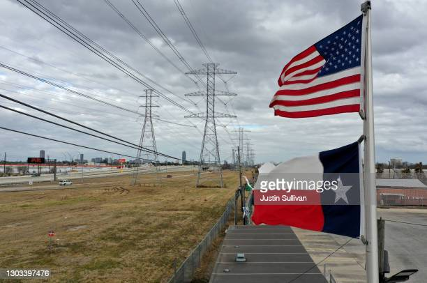 The U.S. And Texas flags fly in front of high voltage transmission towers on February 21, 2021 in Houston, Texas. Millions of Texans lost power when...