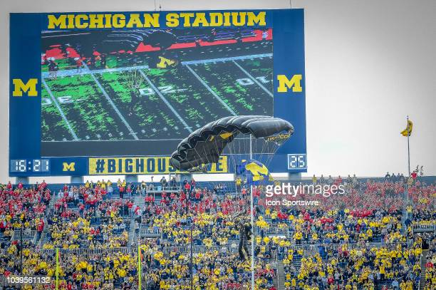 The US Army SOCOM ParaCommandos perform a landing with the US Flag and University of Michigan Flag prior to the Michigan Wolverines versus Nebraska...