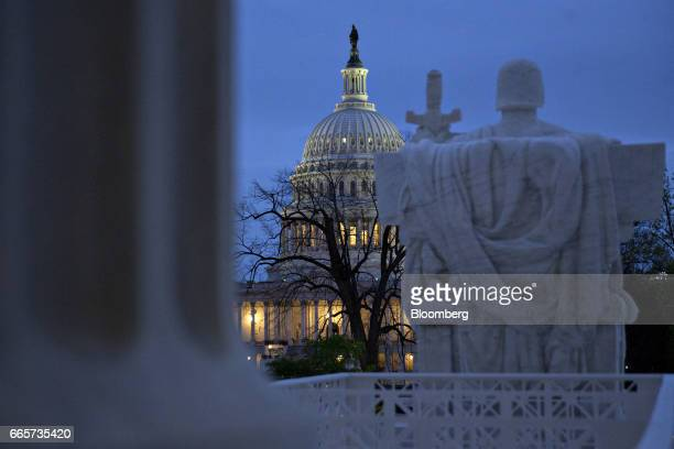The US Capitol building stands past the 'Authority of Law' statue at the US Supreme Court building in Washington DC US on Friday April 7 2017 Judge...