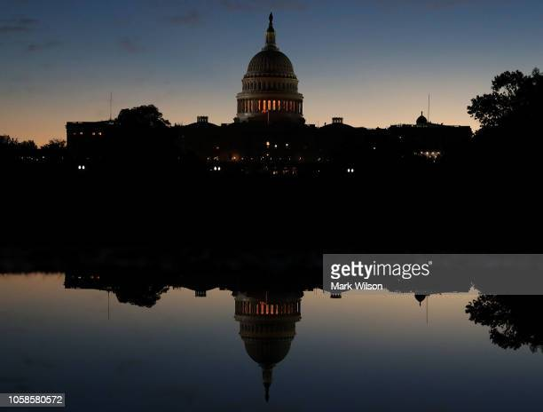 The US Capitol is reflected in a puddle of water a day after Americans voted in the midterm elections on November 7 2018 in Washington DC Democrats...