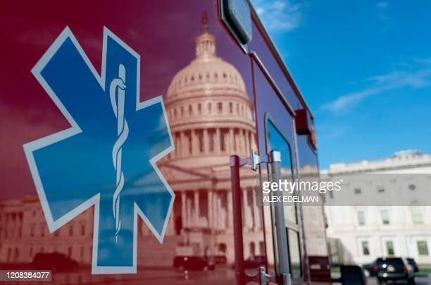 The US Capitol is reflected in a standby ambulance on March 27 in Washington, DC. - The US House of Representatives is expected to vote on a COVID-19...