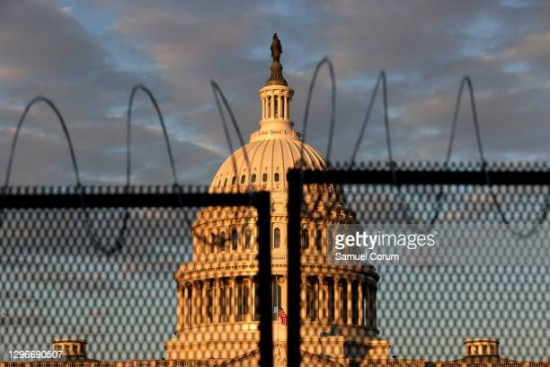 The U.S. Capitol is seen behind a fence with razor wire during sunrise on January 16, 2021 in Washington, DC. After last week's riots at the U.S....