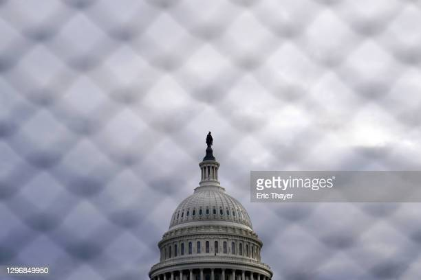 The U.S. Capitol is seen behind fences on January 17, 2021 in Washington, DC. After last week's riots at the U.S. Capitol Building, the FBI has...