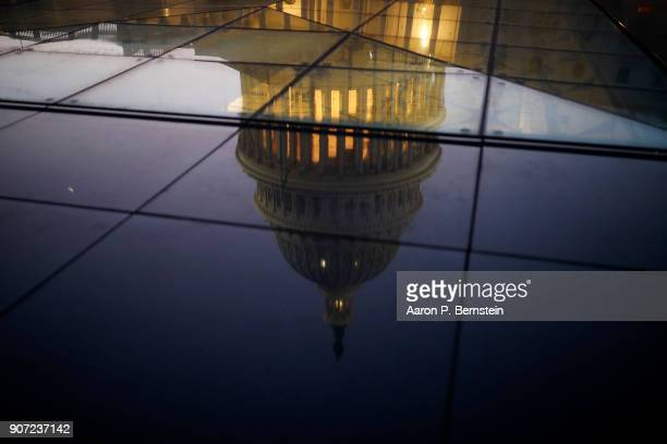 The US Capitol is seen reflected in the windows of the Capitol Visitors Center as lawmakers work to avert a government shutdown January 19 2018 in...