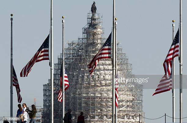 The US Capitol seen through American Flags surrounding the Washington Monument as they stand at half mast in Washington DC November 16 to honor the...