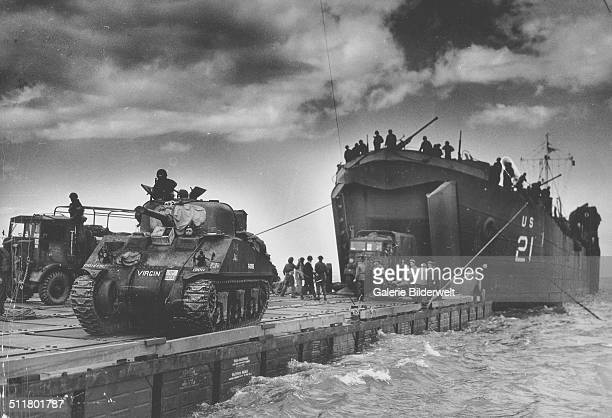 """The U.S. Coast Guard manned USS LST-21 unloads British Army tanks and trucks onto a """"Rhino"""" barge during the early hours of the invasion on Gold..."""
