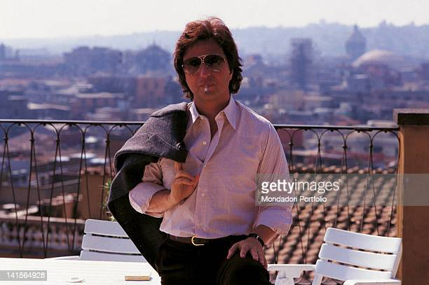 The US director Michael Cimino while is smoking on a terrace behind him a city landscape Italy the '70s