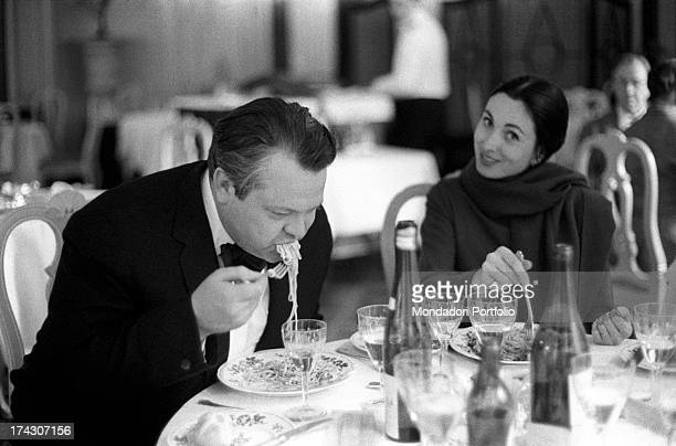 the US film director Orson Welles eats a plate of spaghetti with tomato sauce in front of a bottle of water and red wine while his third wife the...