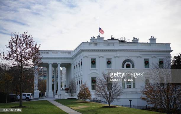 The US flag above the White House flies at halfstaff in honor of former US President George HW Bush in Washington DC on December 3 2018 Bush died on...