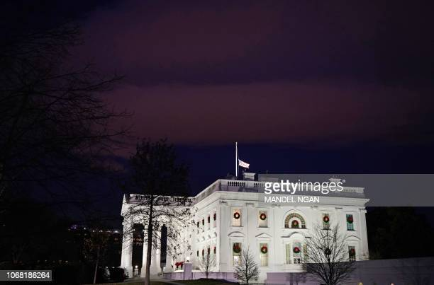 The US flag above the White House flies at halfstaff in honor of former US President George H W Bush in Washington DC on December 3 2018 The body of...