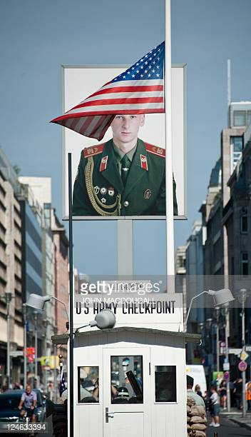 The US flag at Berlin's Checkpoint Charlie flies at half mast in front of a portrait of a Russian soldier September 11 on the tenth anniversary of...