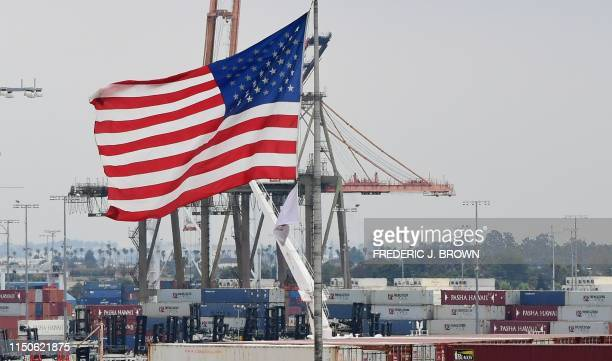 The US flag fies in the foreground as containers are seen at the Port of Los Angeles on June 18 2019 in San Pedro California where the USChina trade...