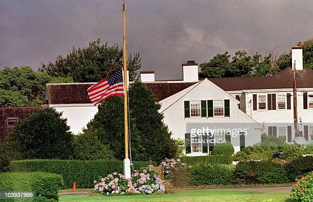 The US flag flies at half mast 20 July 1999 outside the Kennedy compound in Hyannis Port Massachusetts The family is mourning the loss of John F...