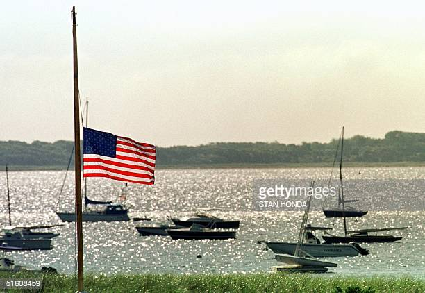 The US flag flies at half mast at the Kennedy compound in Hyannis Port Massachusetts 20 July as sail boats sit anchored in the harbor The Kennedy...