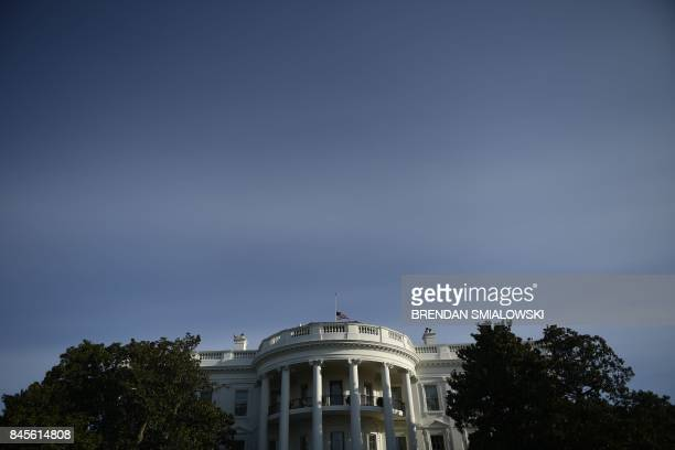 The US flag flies at halfmast at the White House before US President Donald Trump and First Lady Melania Trump observe a moment of silence on...
