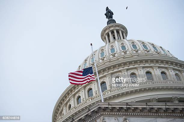 The US flag flies at halfstaff at the Capitol in Washington DC on December 7 2016 to honor the victims of the Japanese attack on Pearl Harbor in...