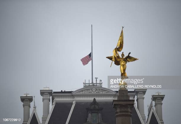 The US flag flies at halfstaff at the Eisenhower Executive Office Building behind the First Infantry Division Monument in tribute to former US...